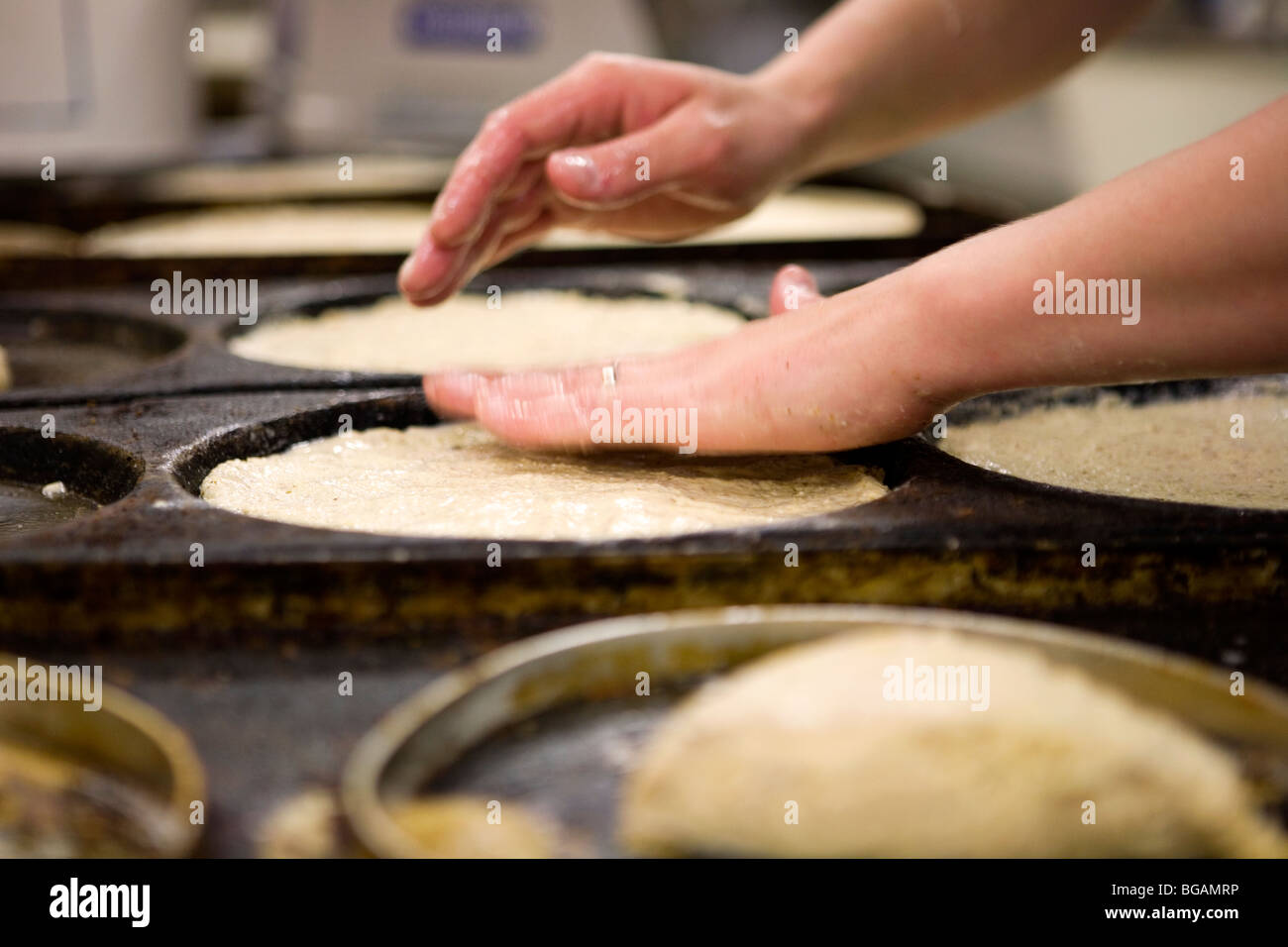 Hands patting down dough for pizza bases in trays - Stock Image