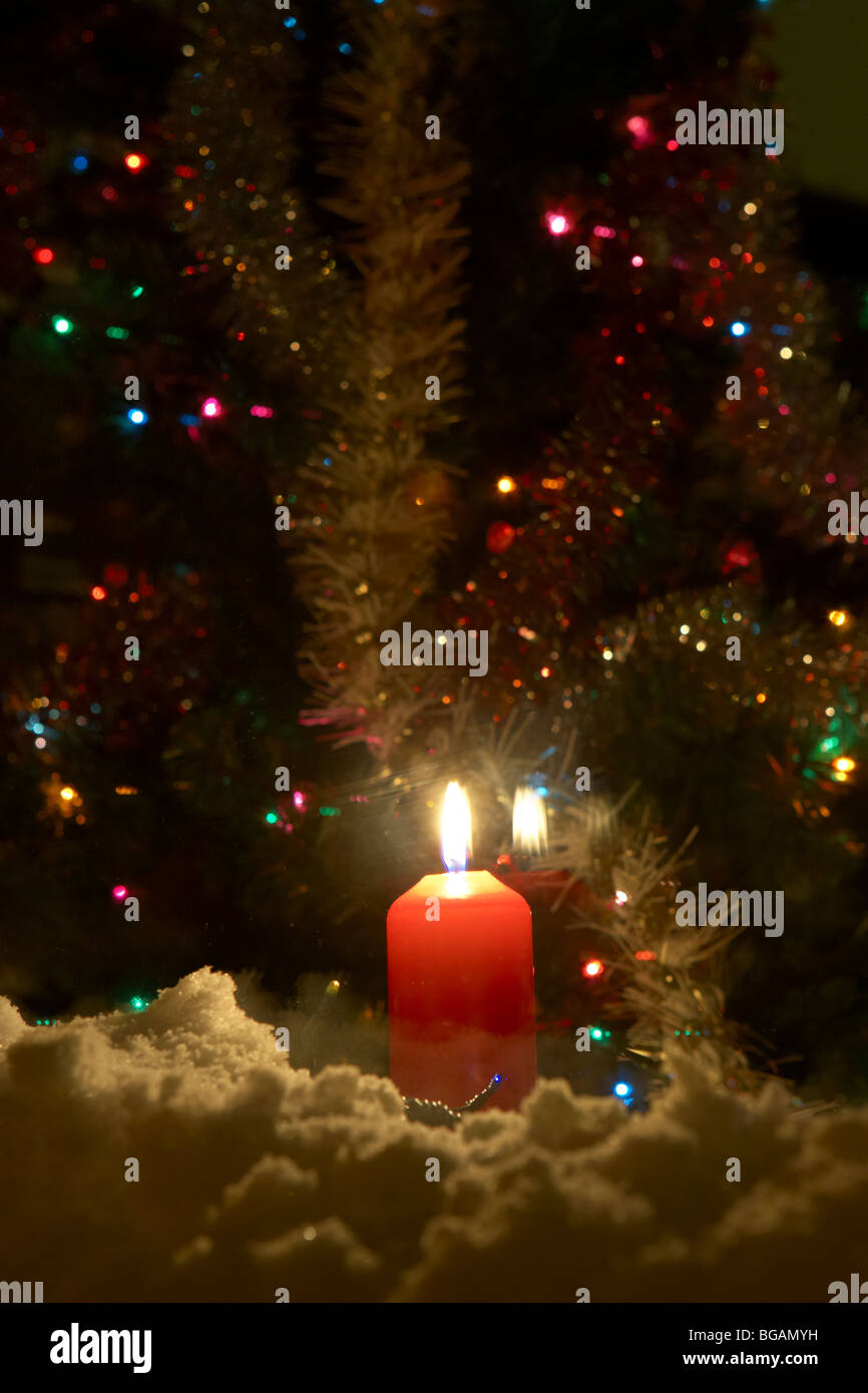 candle burning in the window of a house with christmas tree in the ...