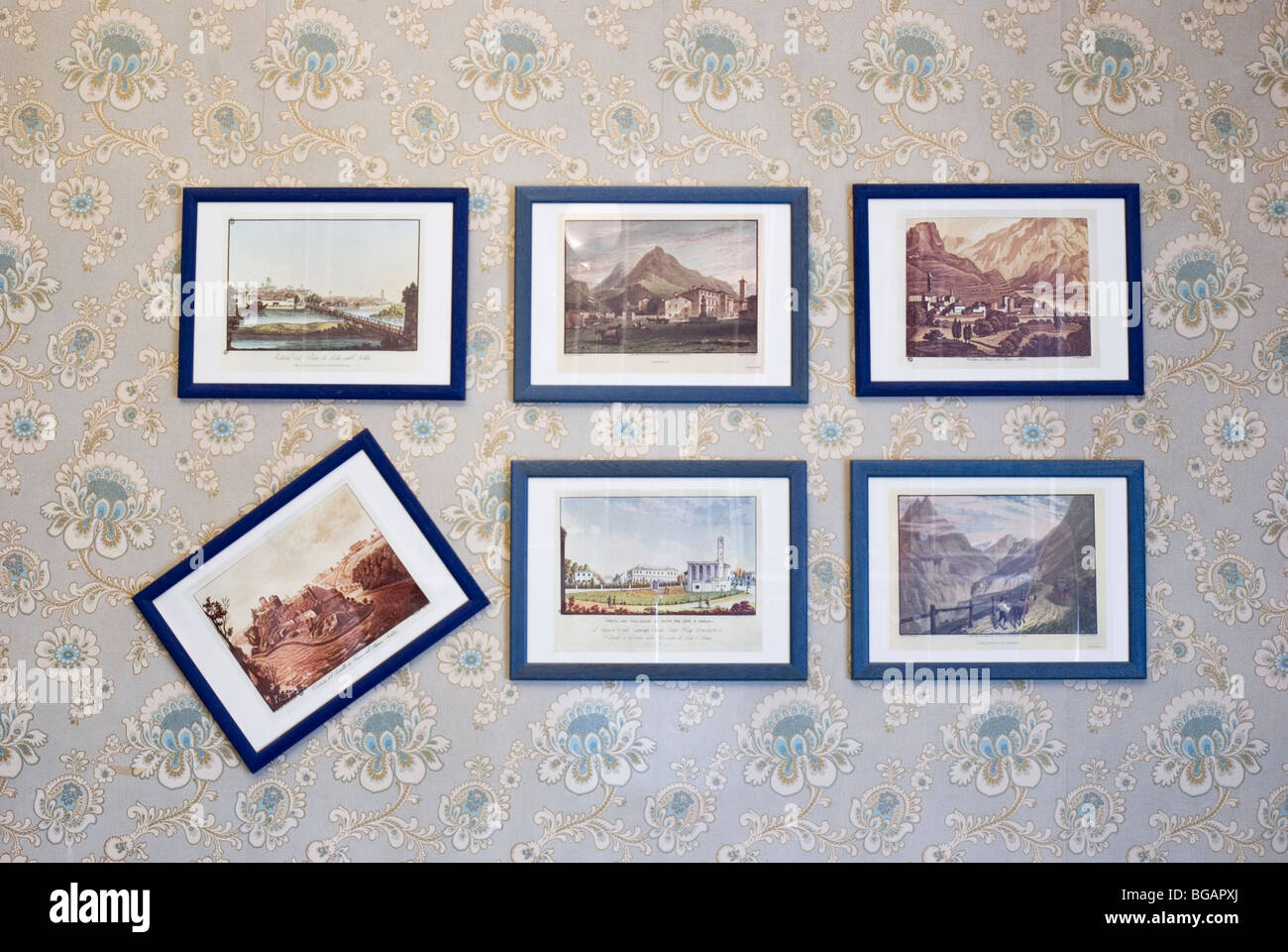 framed painting in a row hanged on wall - Stock Image