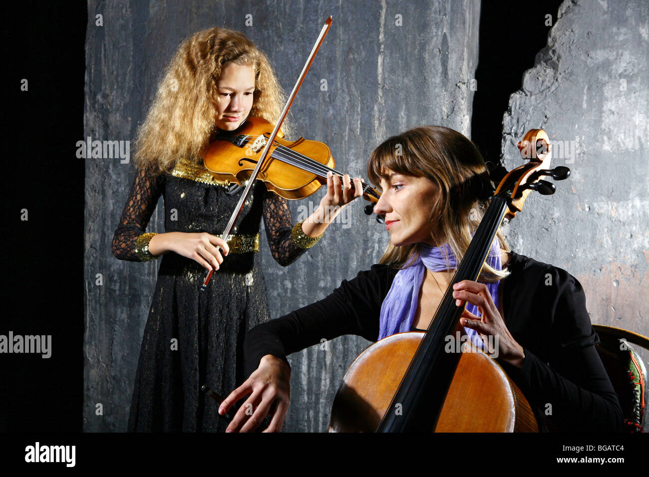 Daughter and mother playing on cello and violin on grey wall background - Stock Image