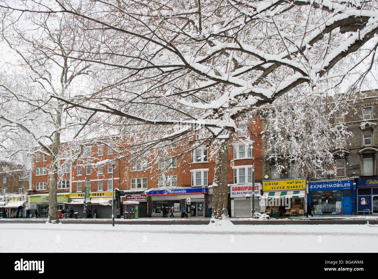 Snow covered street and branches of a tree in Shepherds Bush Green London England - Stock Image
