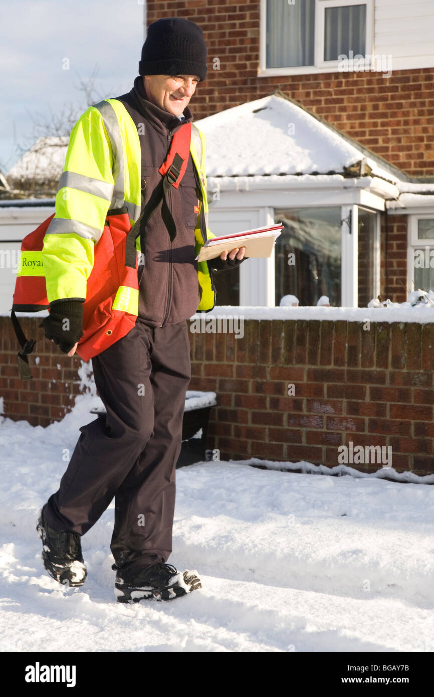 A postman makes his Christmas deliveries despite the snowfall which has affected road conditions in the north of Stock Photo