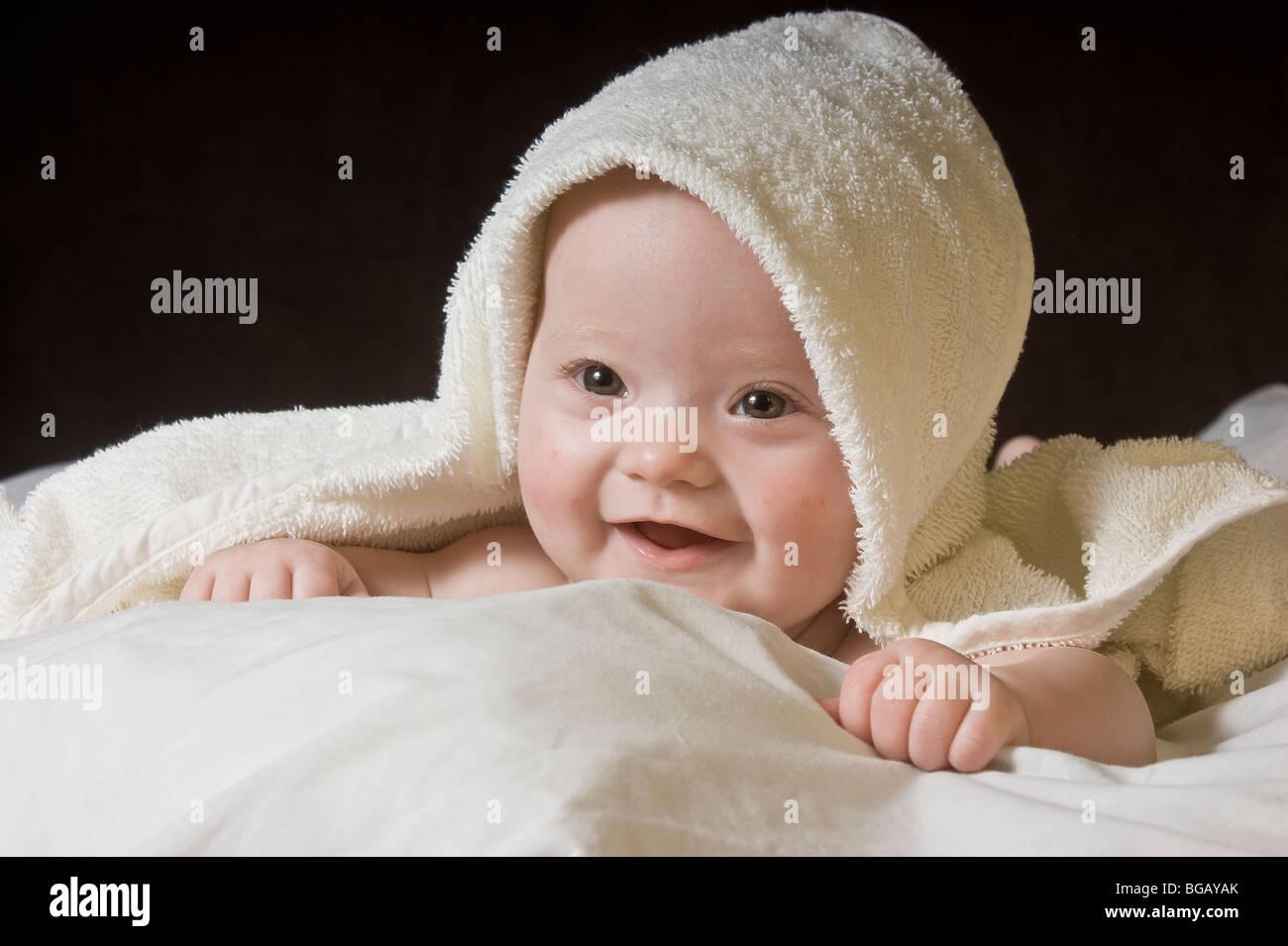 Baby lying on bed - Stock Image