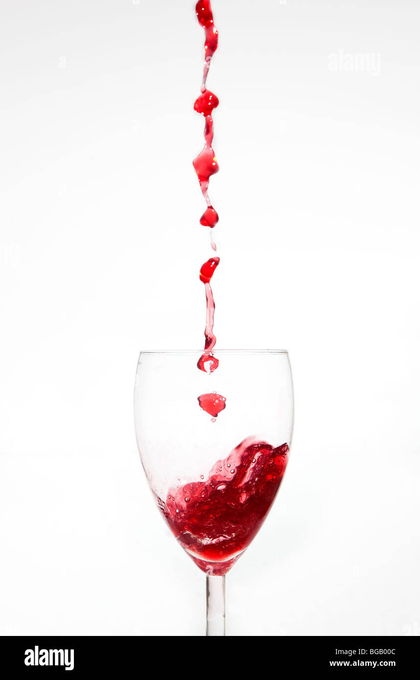 Wine drops falling in to glass - Stock Image