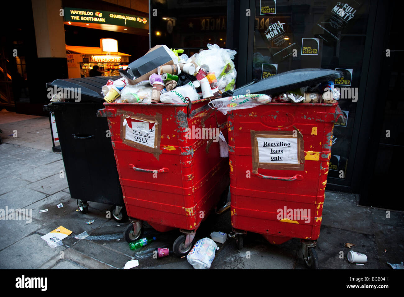 Recycling bins overflowing with rubbish. Designed  to recycle waste, these bins are now loaded with trash. Stock Photo