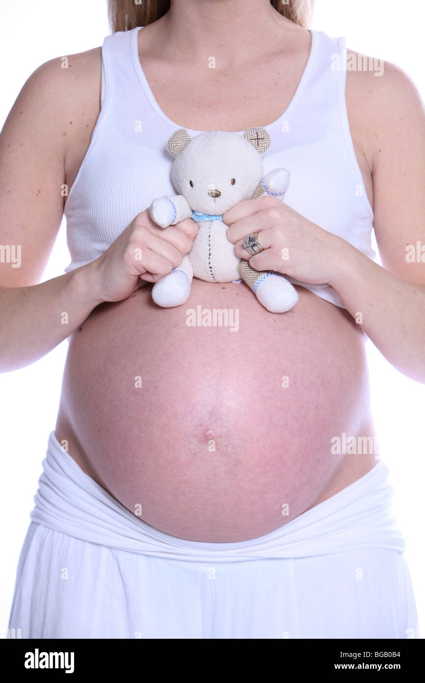 Pregnant woman holding teddy bear on her bare belly - Stock Image