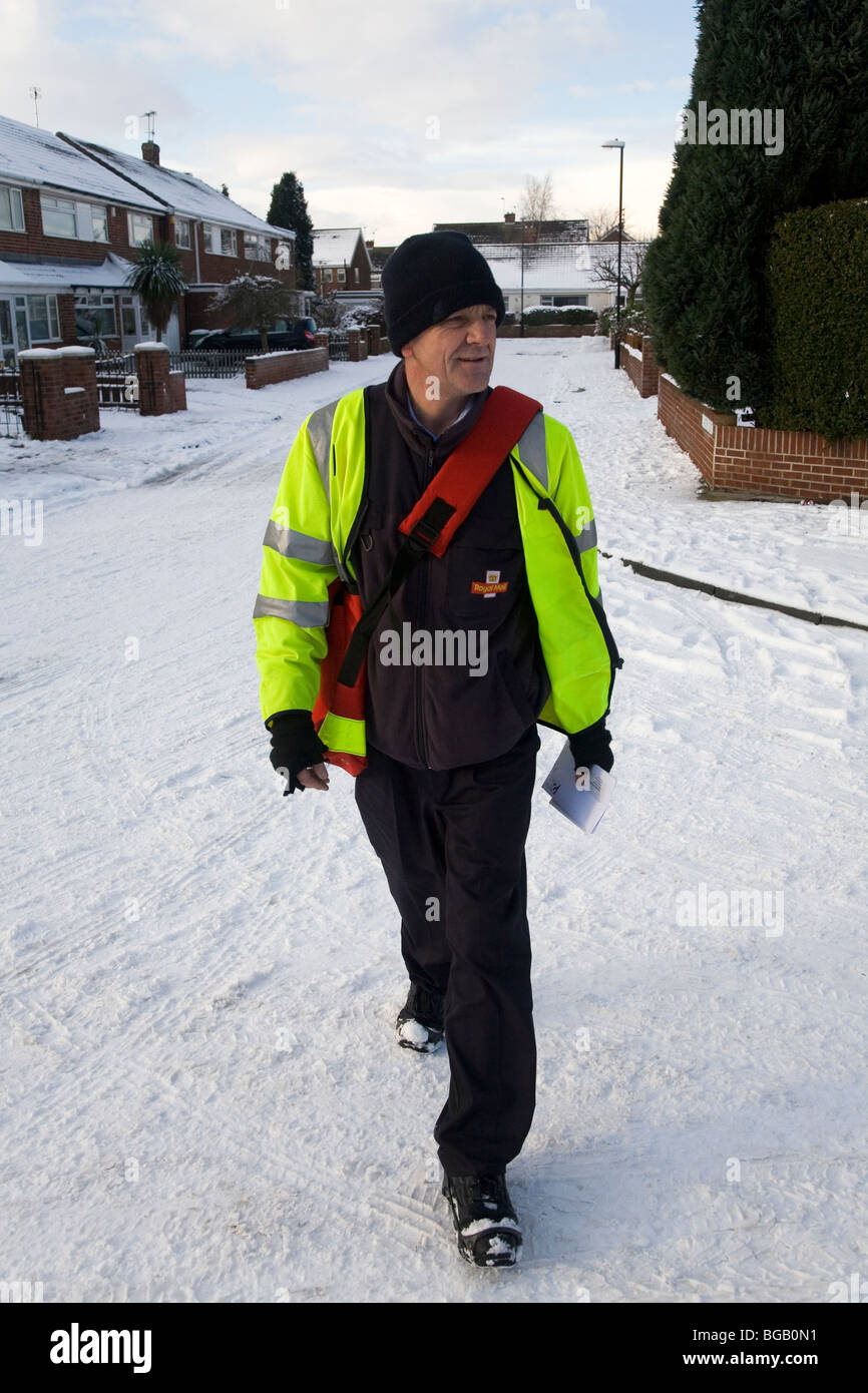 A postman makes his Christmas deliveries despite the snowfall which has affected road conditions in the north of - Stock Image