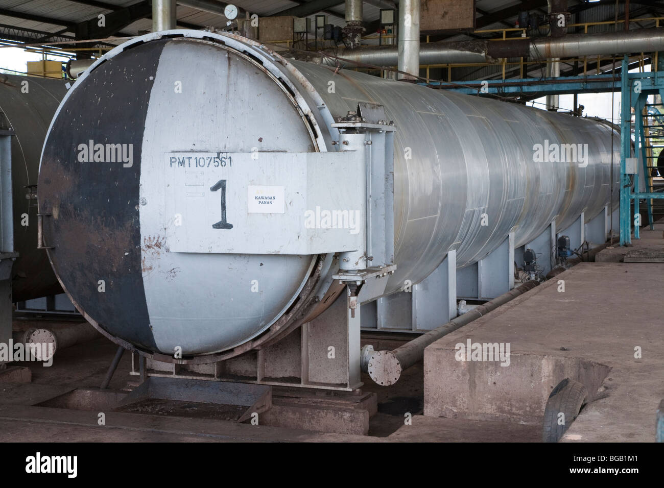 The large cooking units sterilize and soften the fresh palm fruit bunches during the first stage of processing. - Stock Image