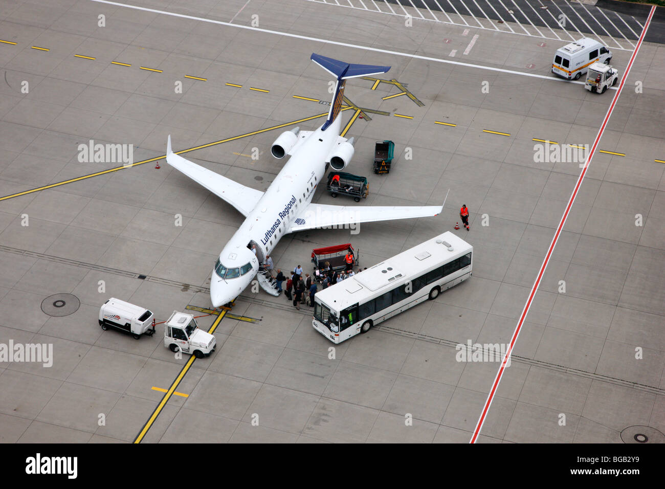 Lufthansa regional jet on Duesseldorf airport, passengers boarding the plane - Stock Image