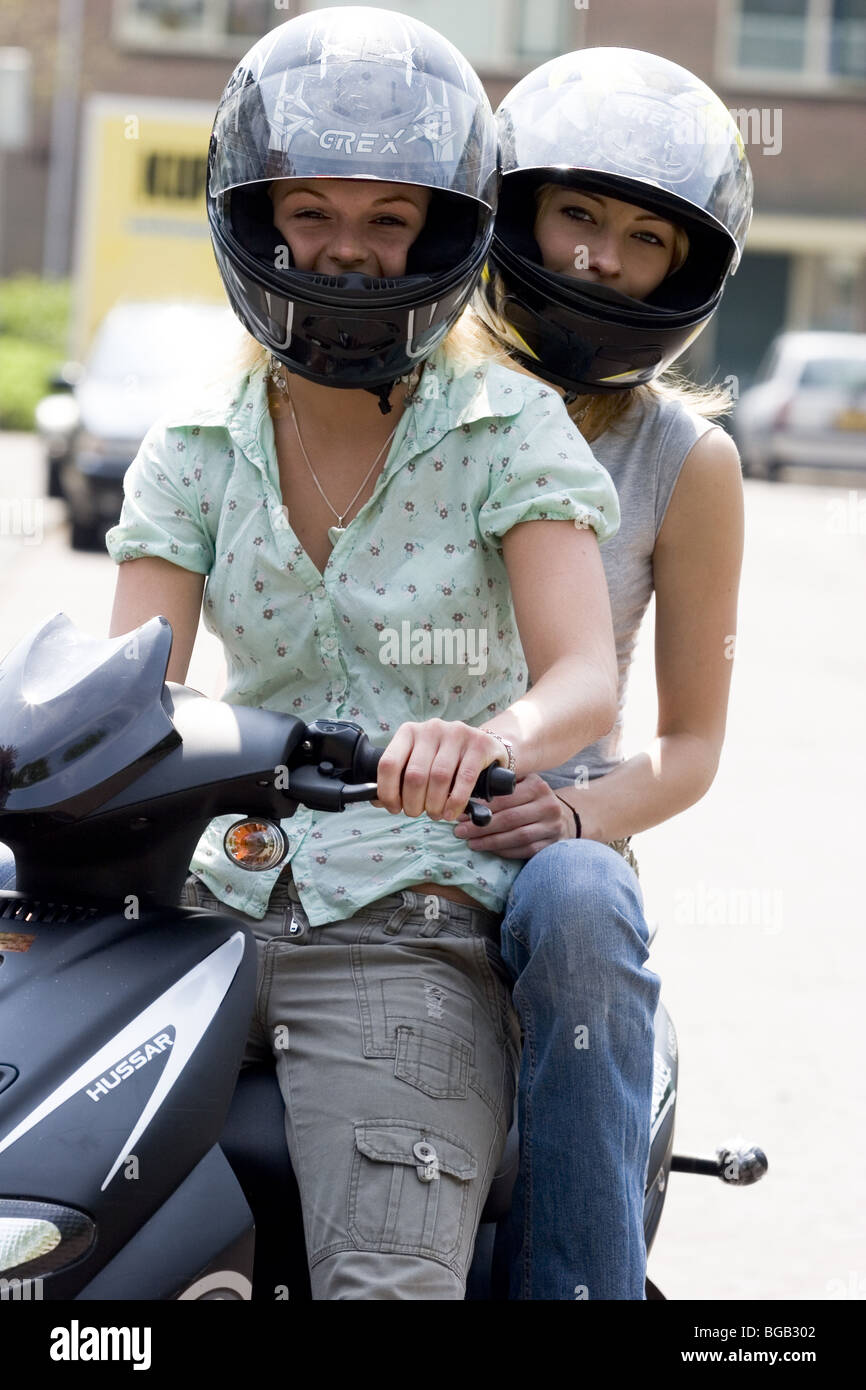 Happy Portrai Two Teenage Girls On Scooter Wearing Safety