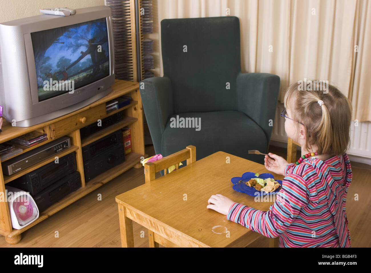 Little girl watching DVDs on television tube in living room, while eating main dinner in front of the tv, shootcvs517003. - Stock Image