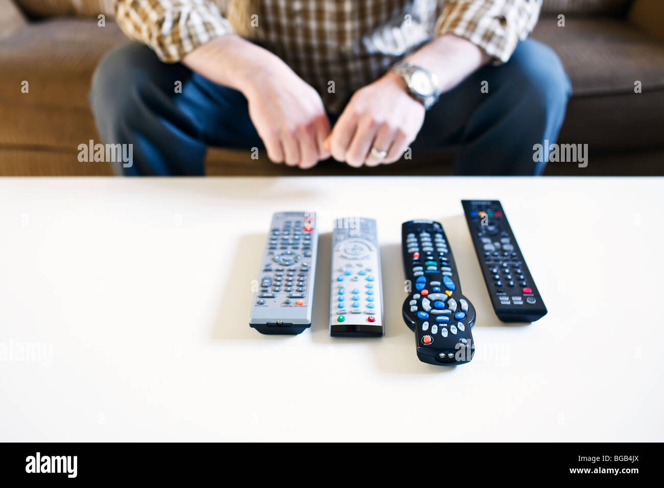 Man sitting on couch, with remote controls lined up on a coffee table. - Stock Image