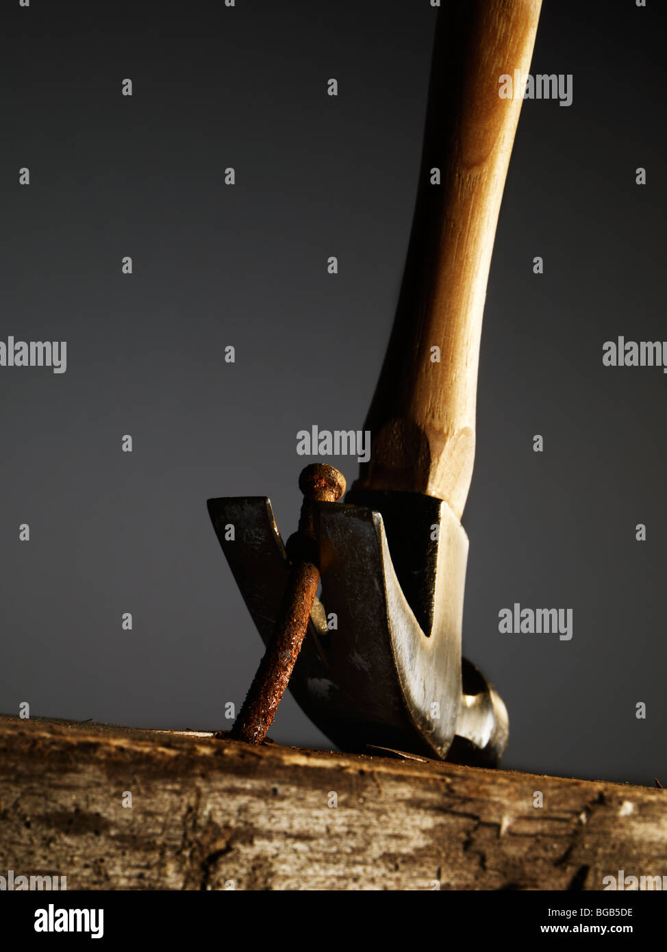 Hammer Removing A Nail From A Old Wooden Surface - Stock Image