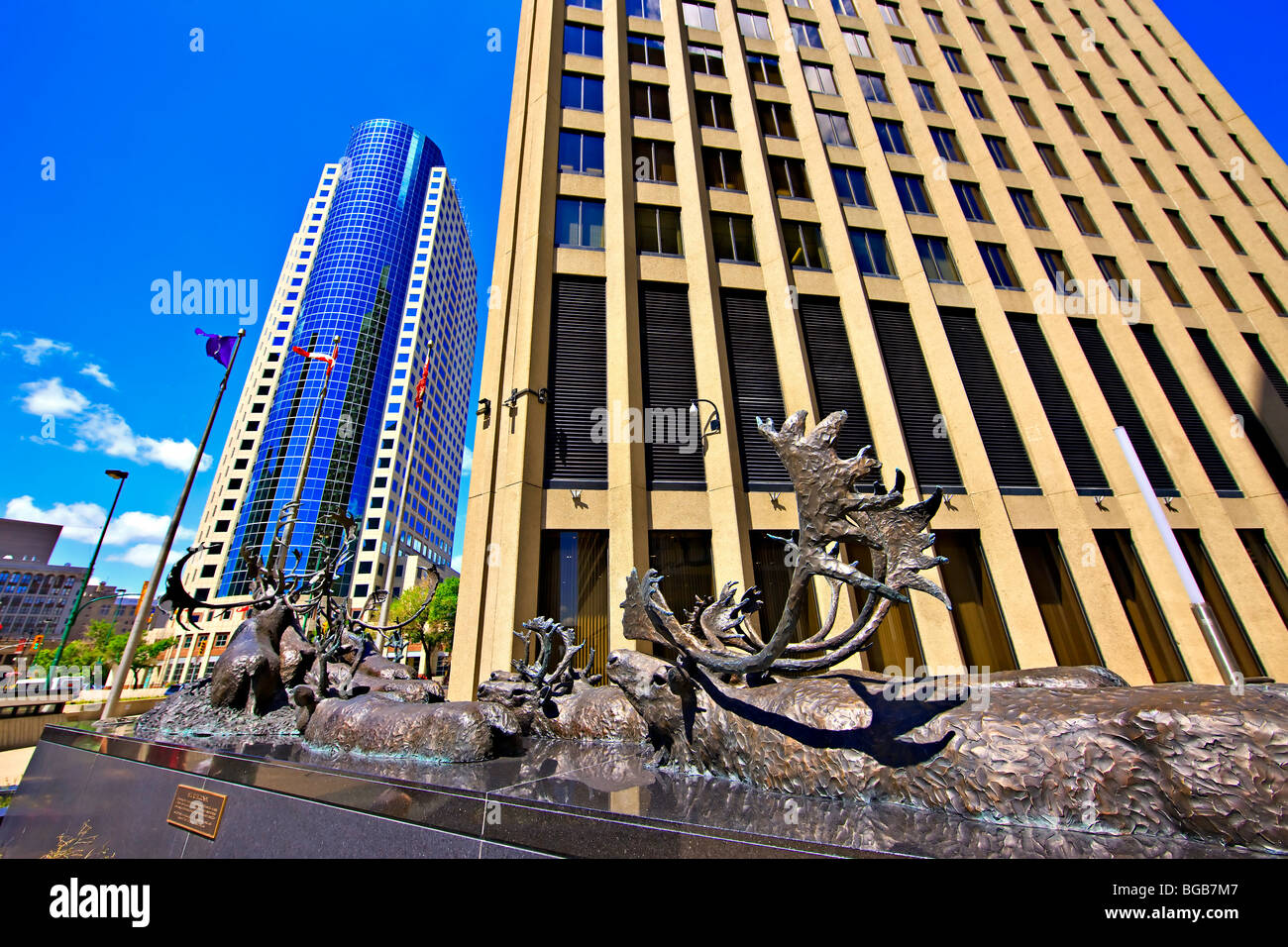 """Bronze sculpture of caribous crossing a river, titled """"Seal River Crossing"""" outside the Richardson Building with the Canwest Pla Stock Photo"""