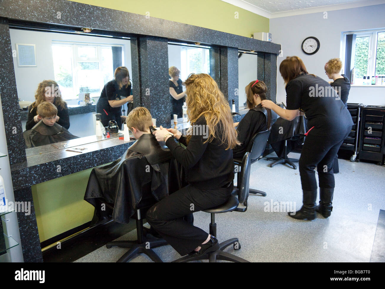 A Hairdresser Cutting Styling A Customers Hair At A