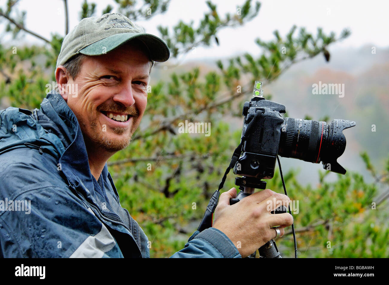 Professional Outdoor Photographer Shooting Photographs in the Rain - Stock Image