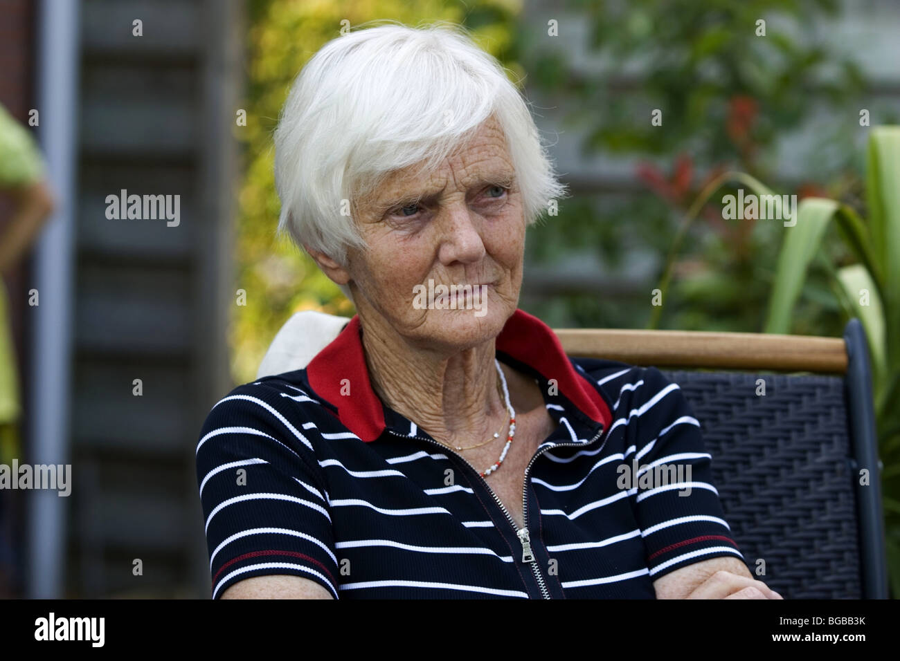 Unhappy elderly woman with white hair contemplating in back garden. - Stock Image