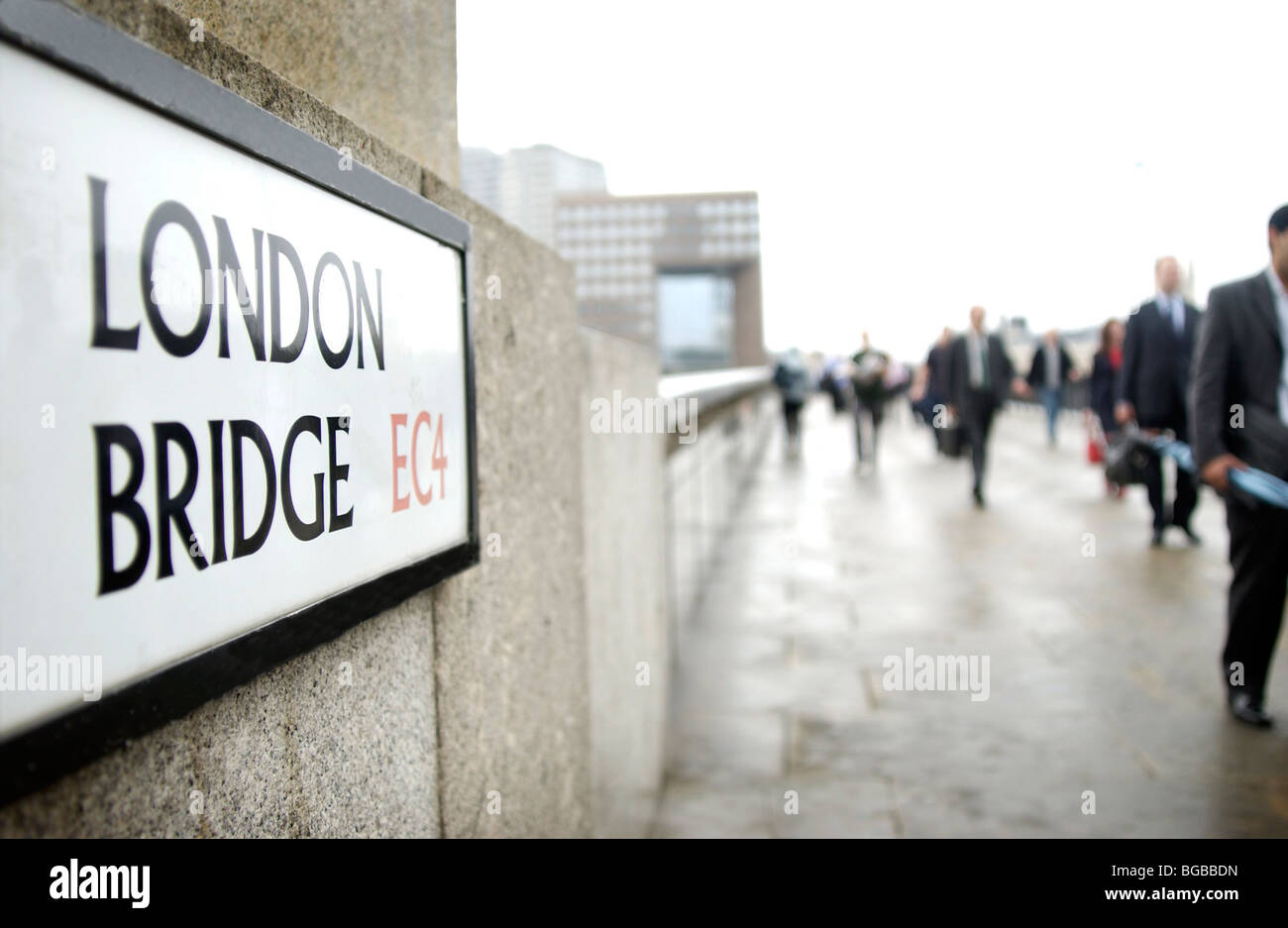 Royalty free photograph of London Bridge with morning commuters walking over it. - Stock Image