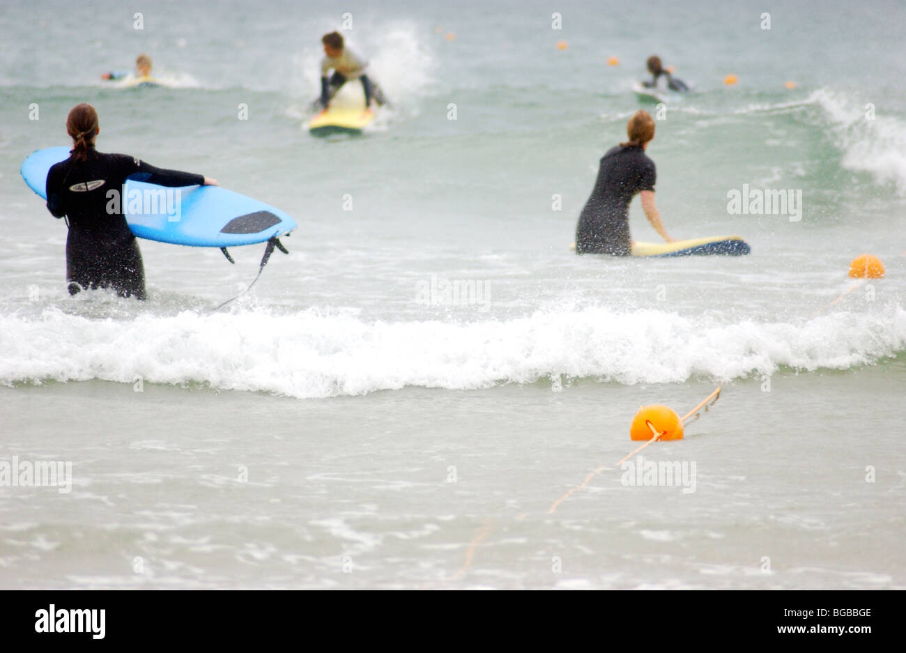 Royalty free photograph of female surfer waiting to go in the sea on a cold winter day in Cornwall UK - Stock Image