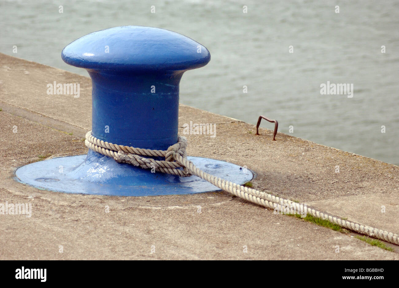 Royalty free photograph of  bollard with rope tied to it at a dock in UK - Stock Image