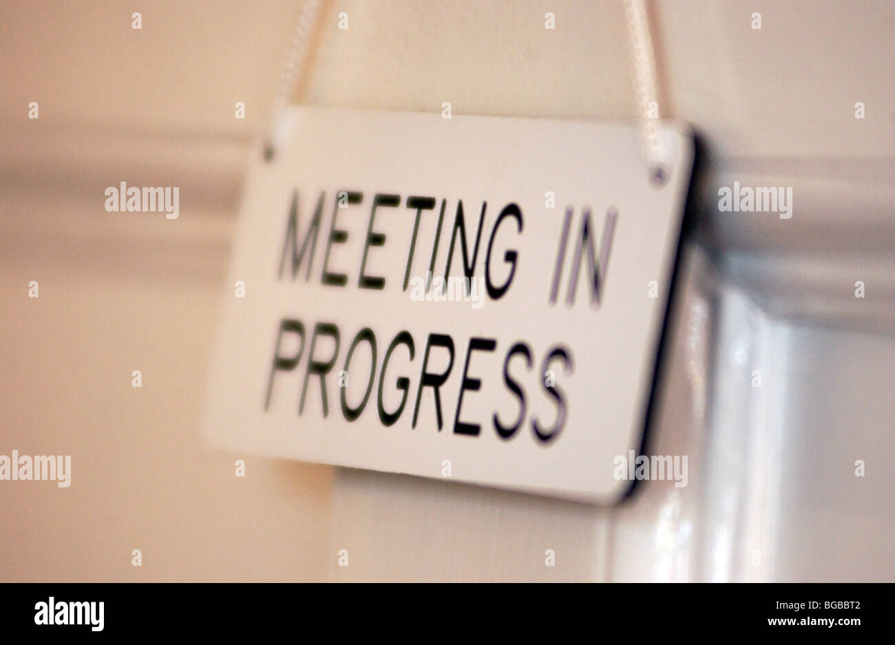 royalty free photograph of meeting in progress sign hanging on door