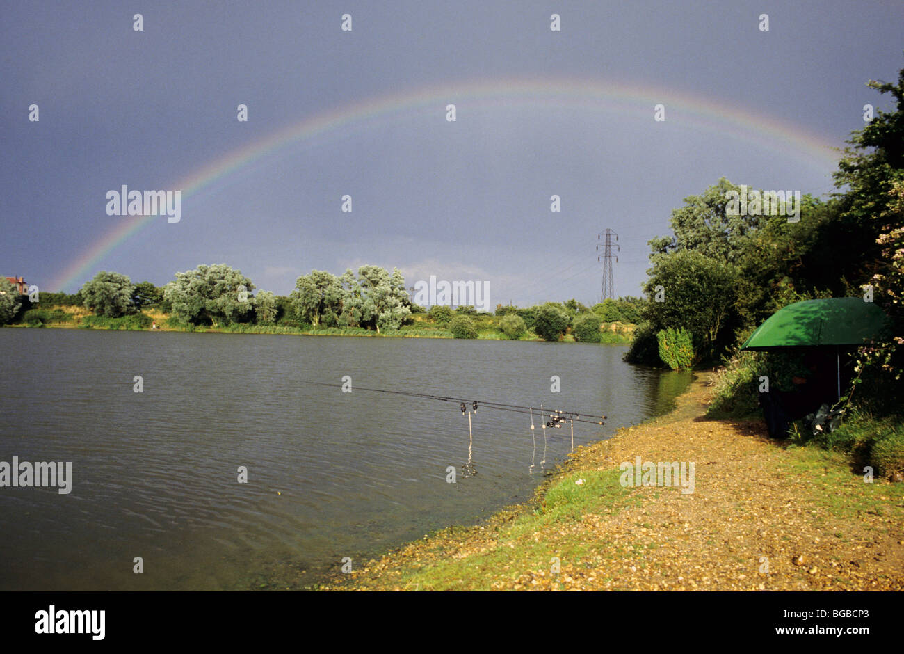 Rainbow over a lake - Stock Image