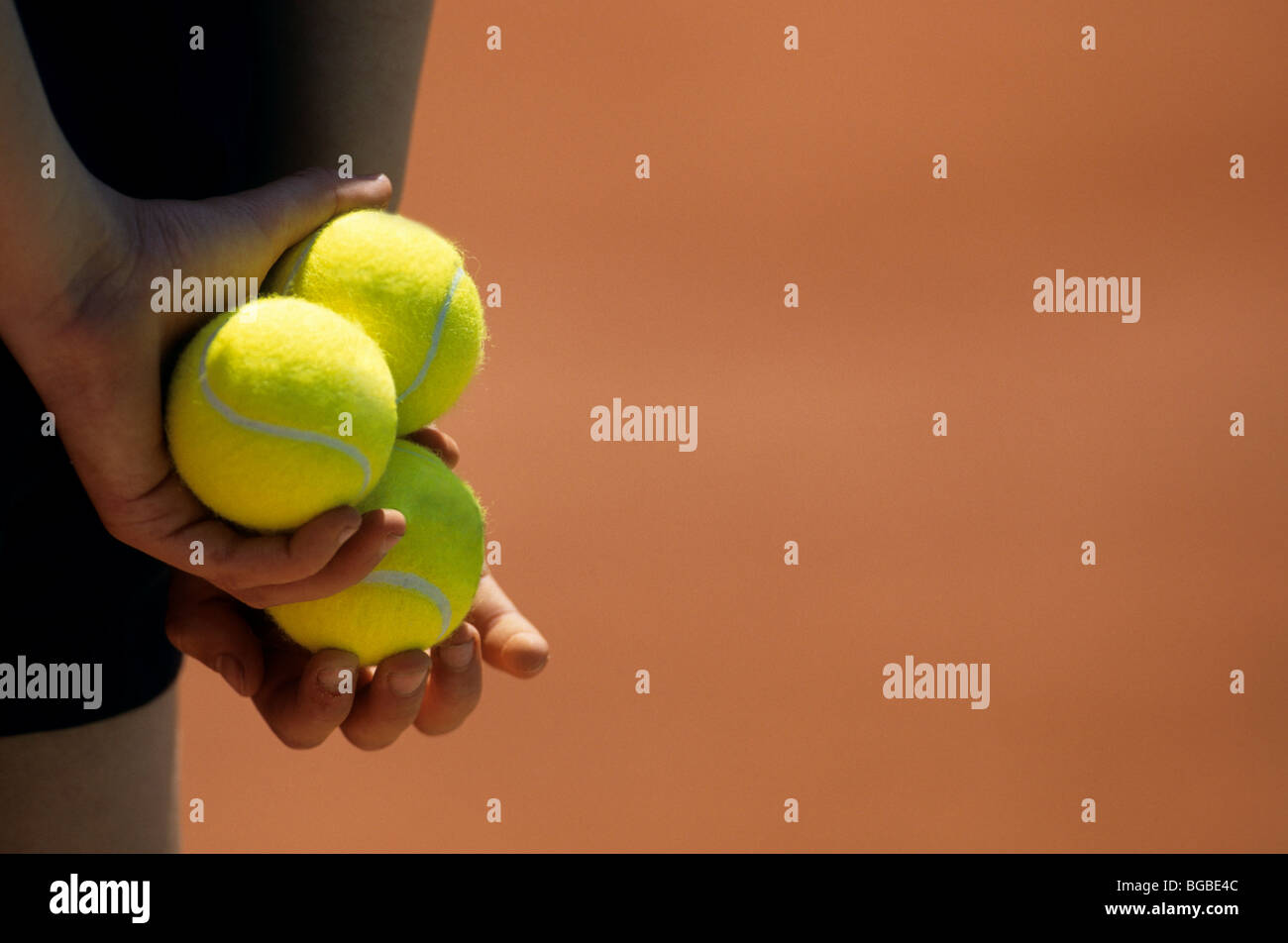 Close up of a ball boy holding tennis balls - Stock Image