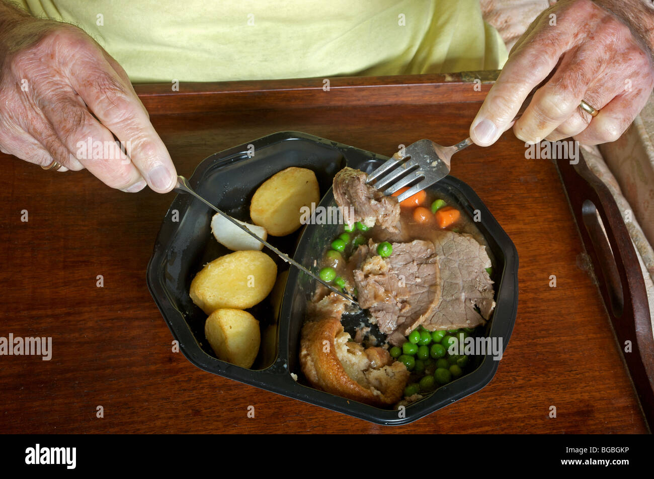 Old age pensioner eating a Birds Eye traditional beef ready meal - Stock Image