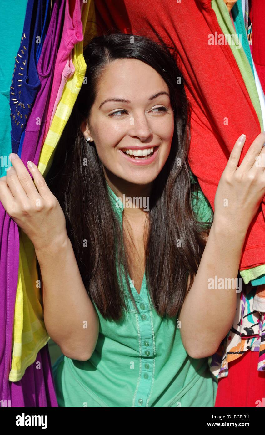 Woman peeping through clothes - Stock Image
