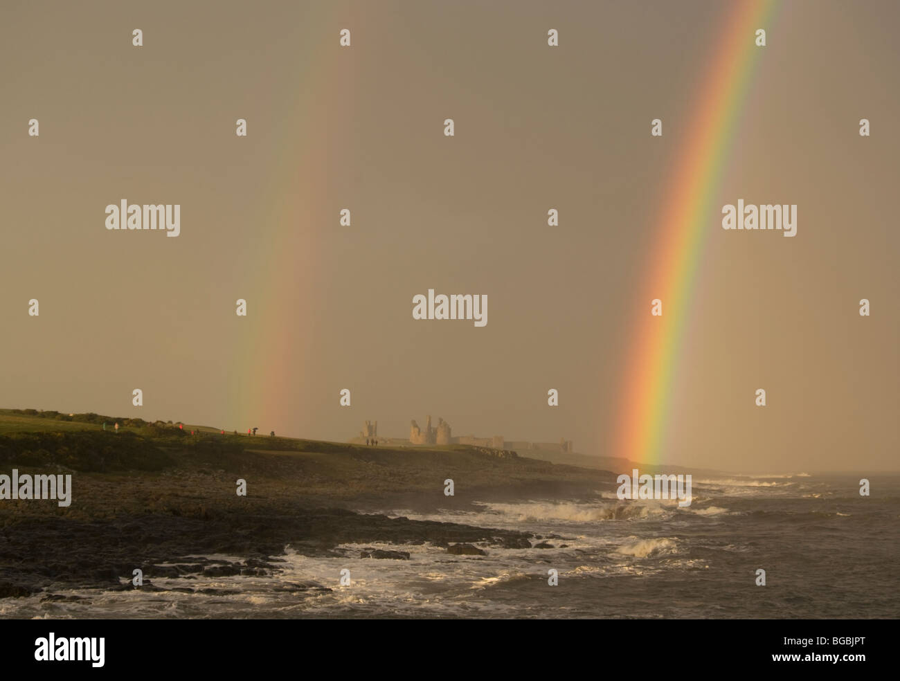 The iconic Dunstanburgh castle is bracketed by twin rainbows - Stock Image