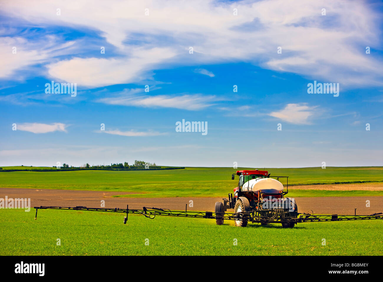 Farmer spraying crops by tractor near the town of Rockglen, Southern Saskatchewan, Canada. - Stock Image