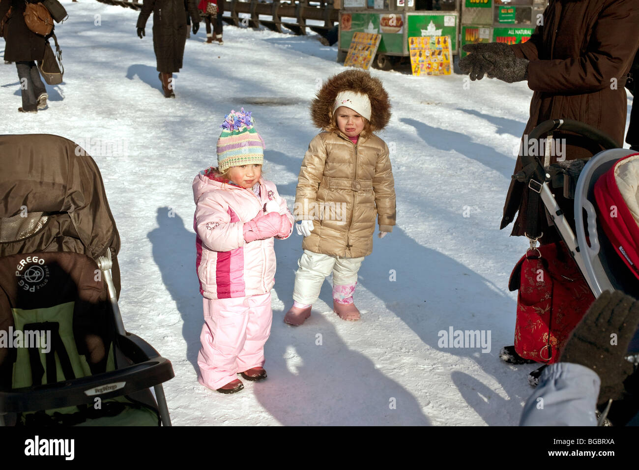two bundled up pretty little girls, one of them very unhappy, stop for a picture on a sunny winter day in snowy - Stock Image