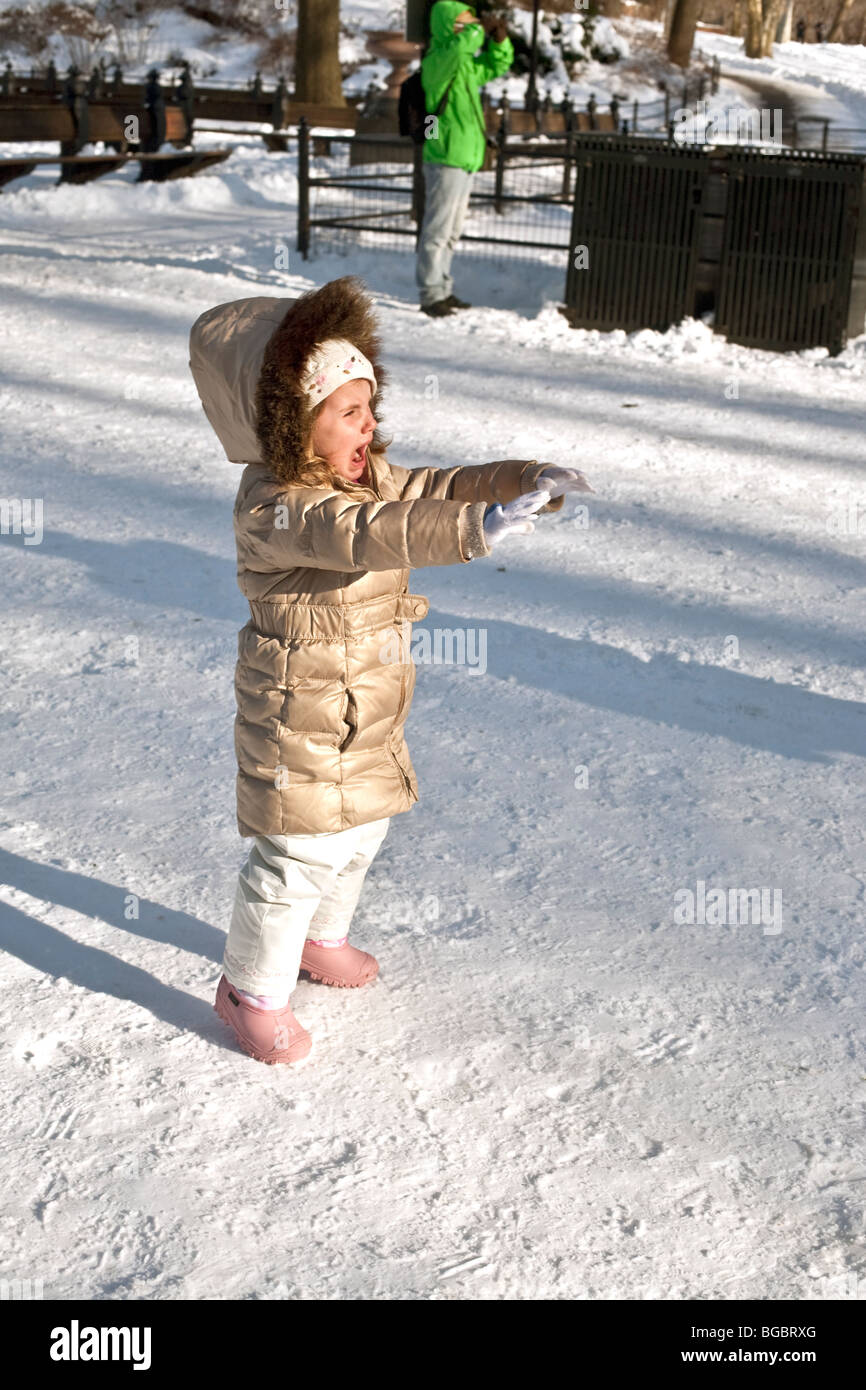 unhappy pretty little girl in gold parka & pink crocs voices her chagrin on a beautiful sunny day in snowy Central - Stock Image