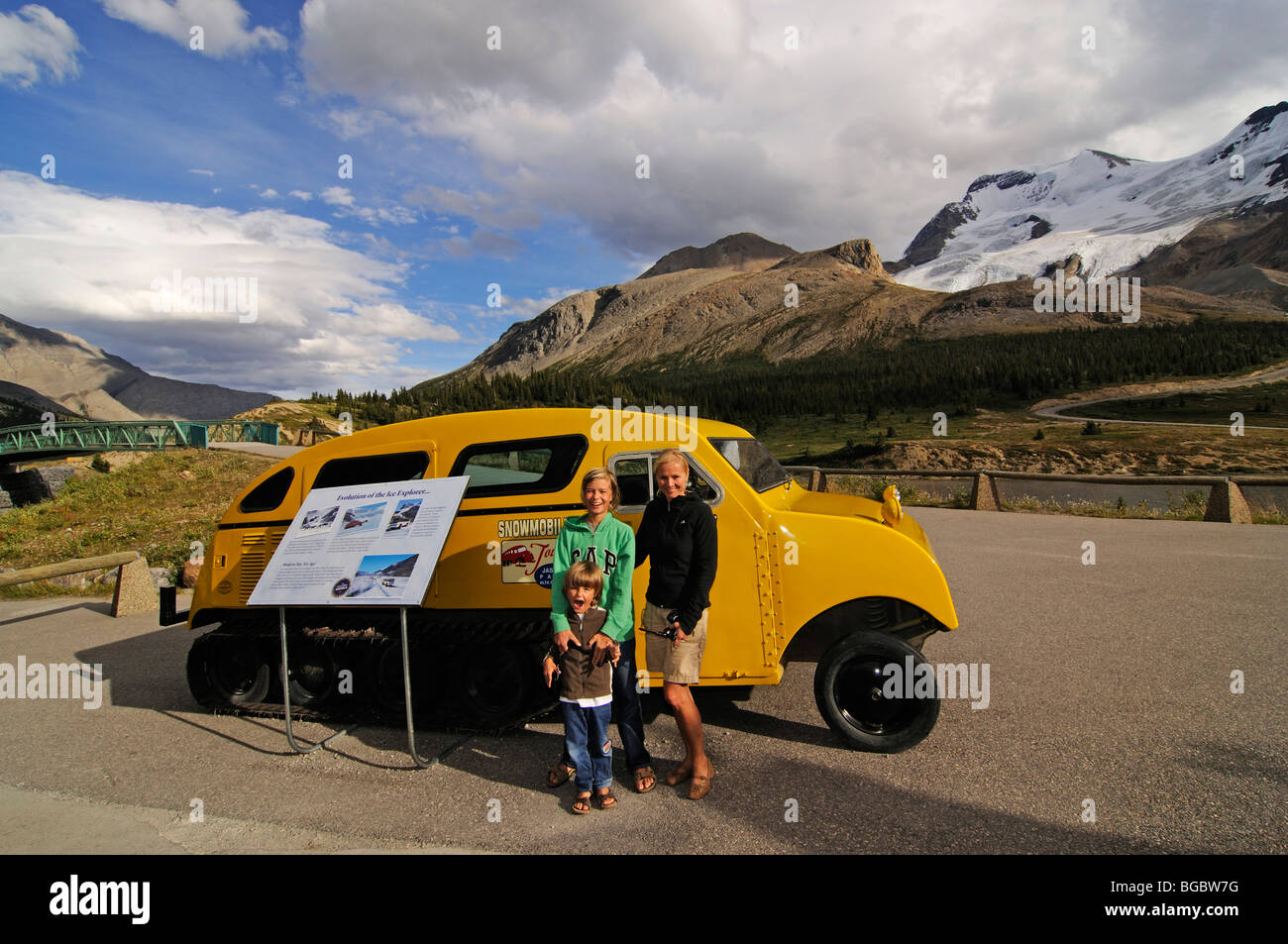 Women and children in front of an old snowmobile, Icefields Parkway, Columbia Icefield, Jasper National Park, Alberta, - Stock Image
