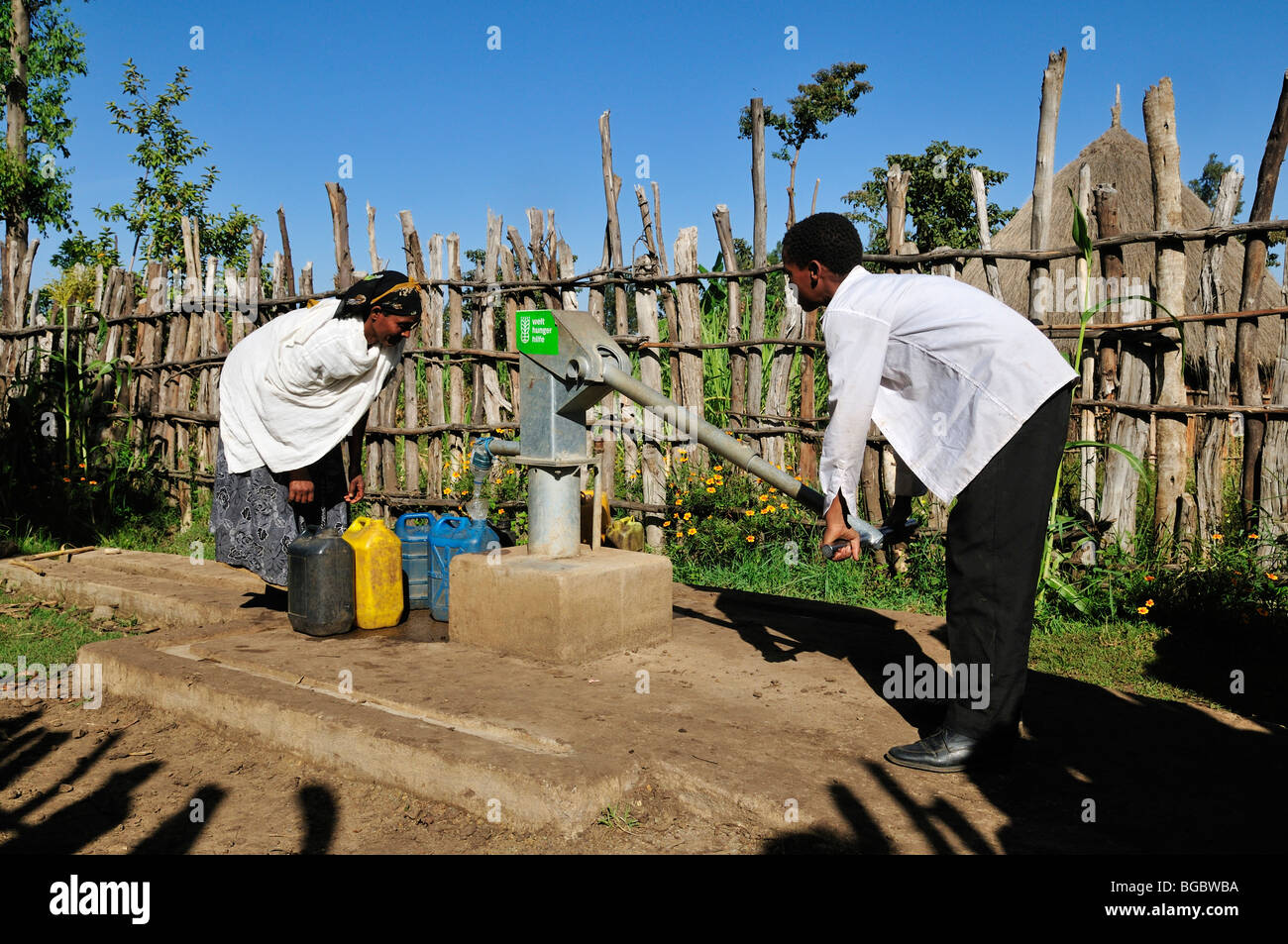 African people pumping water at a newly built waterpump, Rift Valley, Oromia, Ethiopia, Africa - Stock Image