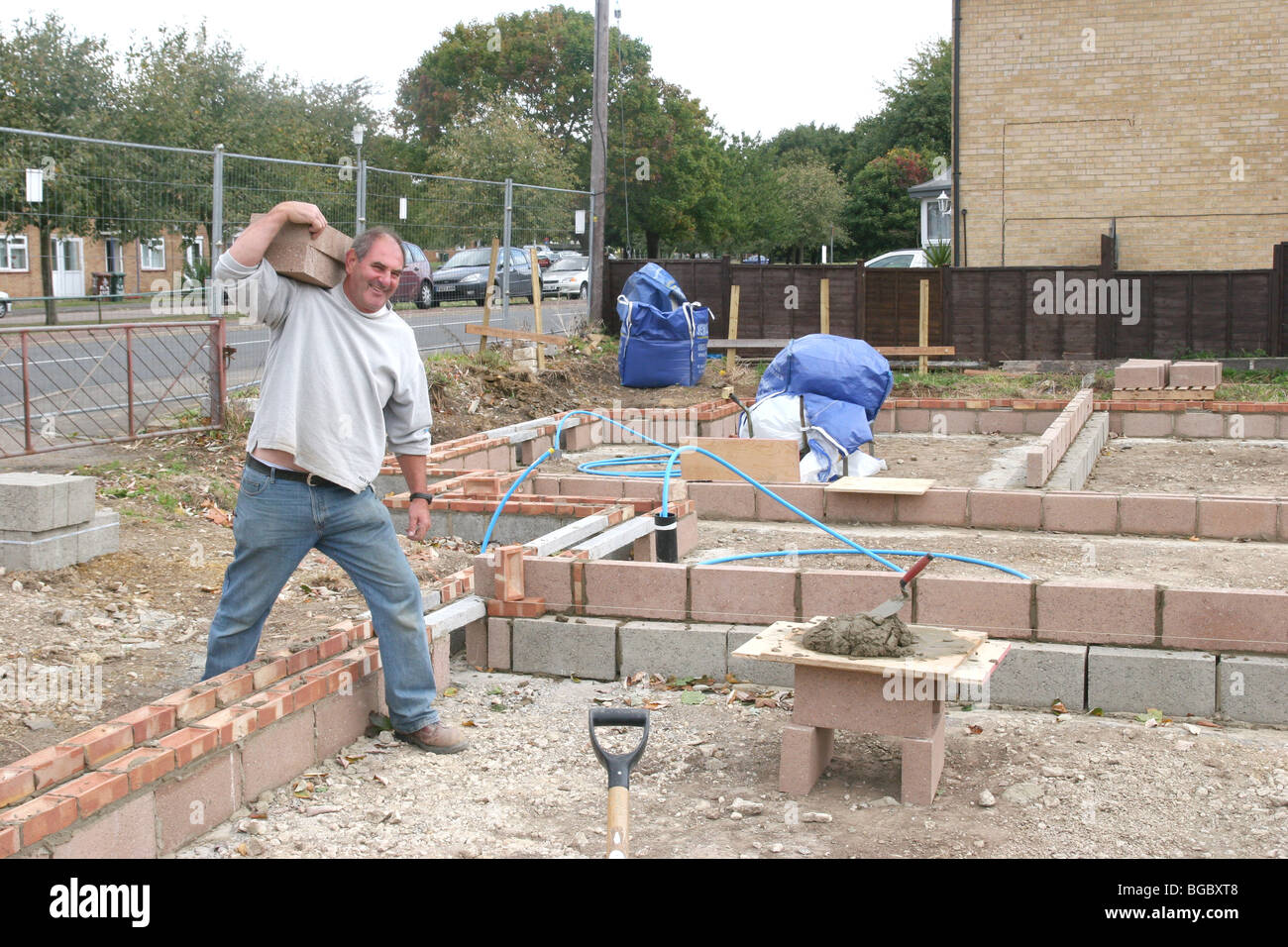 A bricklayer carrying bricks on a building site in the UK. - Stock Image