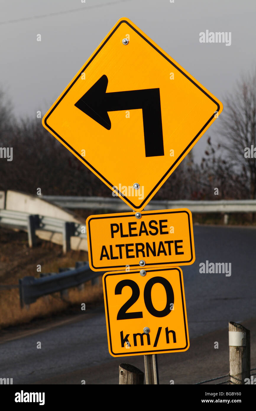 Sharp Left Turn, Speed Limit and Please Alternate Signs at Bridge Entrance - Stock Image