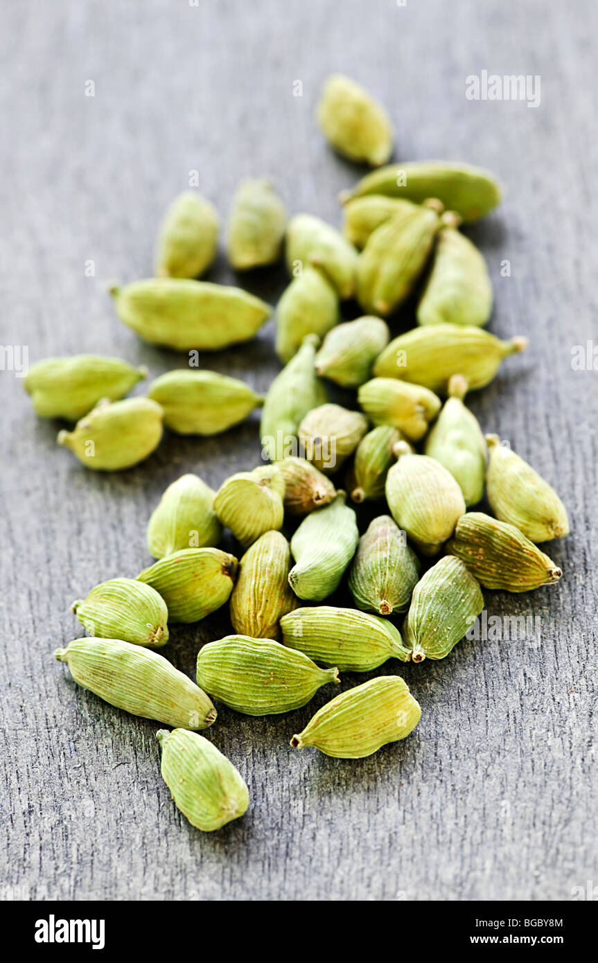 Several whole green cardamom seed pods on wooden background - Stock Image