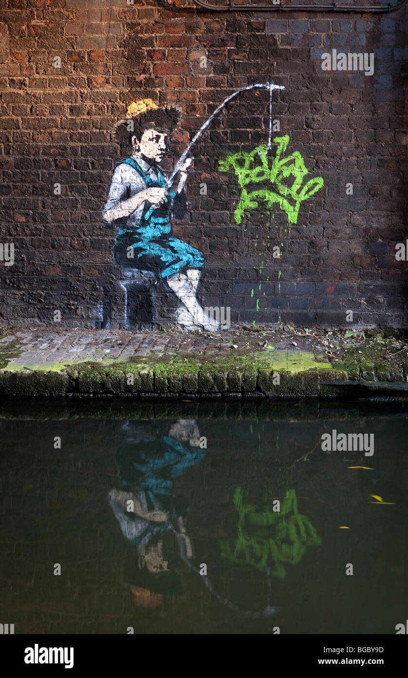 Banksy image of Huckleberry Finn character New graffiti in Camden Lock on Grand Union cannal London UK. - Stock Image