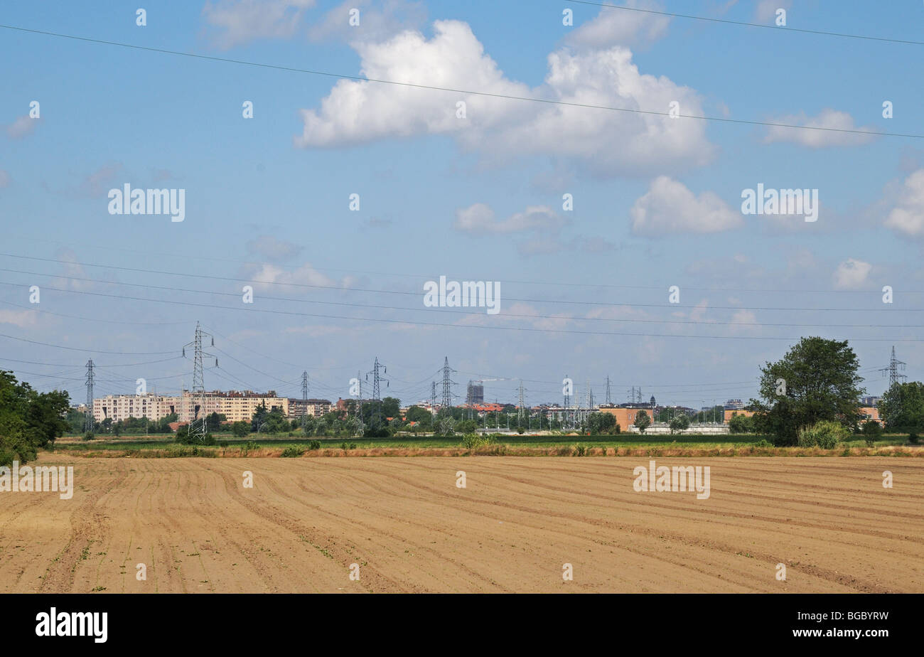 High voltage power cables wires and pylons crossing farm land in the foreground Southern periphery of Milan Lombardy - Stock Image