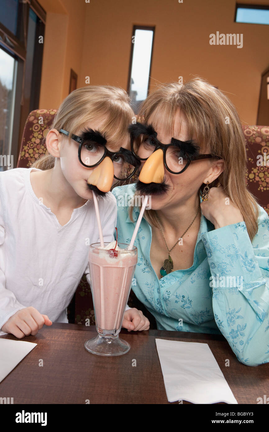 Mother and daughter share milkshake in disguise - Stock Image