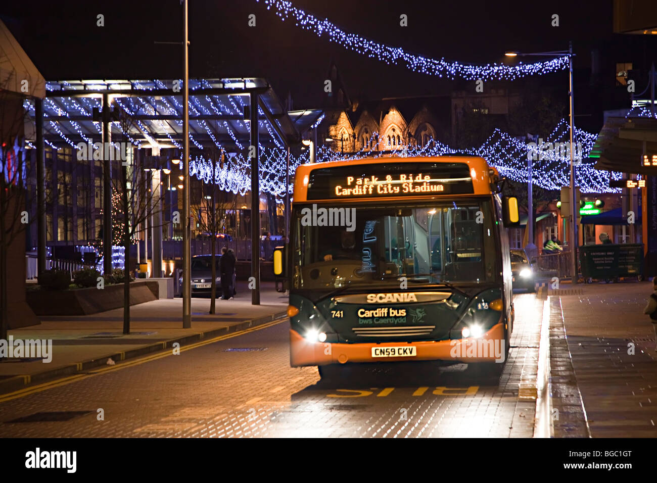 Public transport bus at night in city centre with Christmas decorations Cardiff Wales UK - Stock Image
