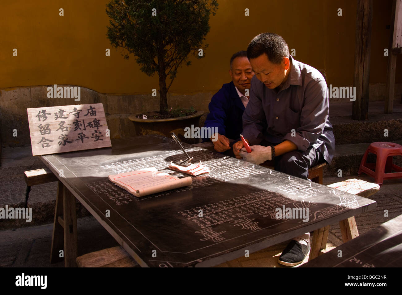 Man engraving the names of contributors of the Zhiyuan temple on a stone tablet. Jiuhua Shan. Anhui province, China. - Stock Image