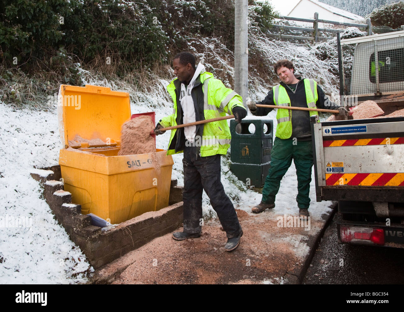 Council workmen filling salt bin from lorry containing grit and salt for roads in village Wales UK - Stock Image