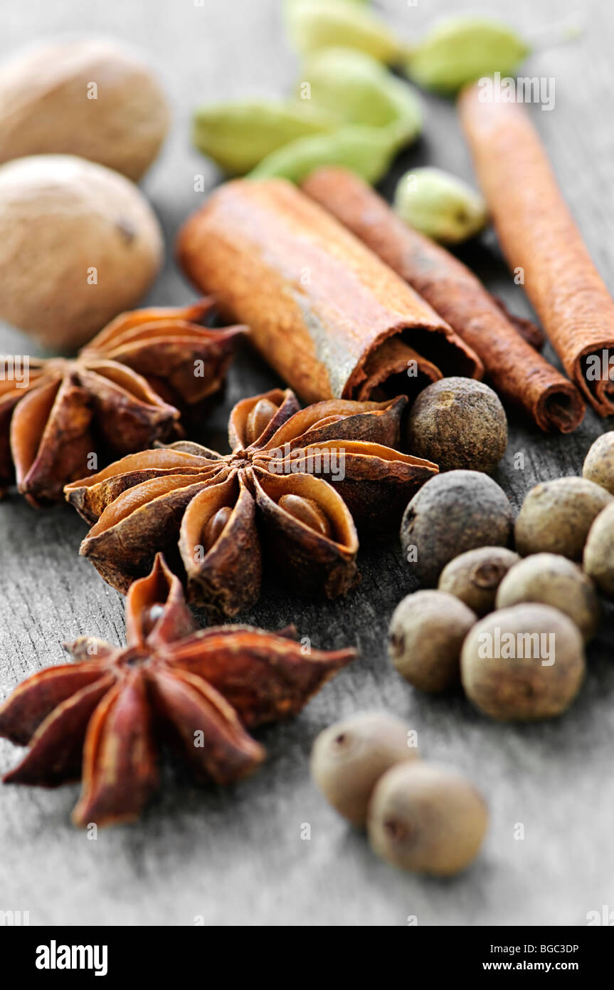 Assorted whole spices close up on wooden background - Stock Image