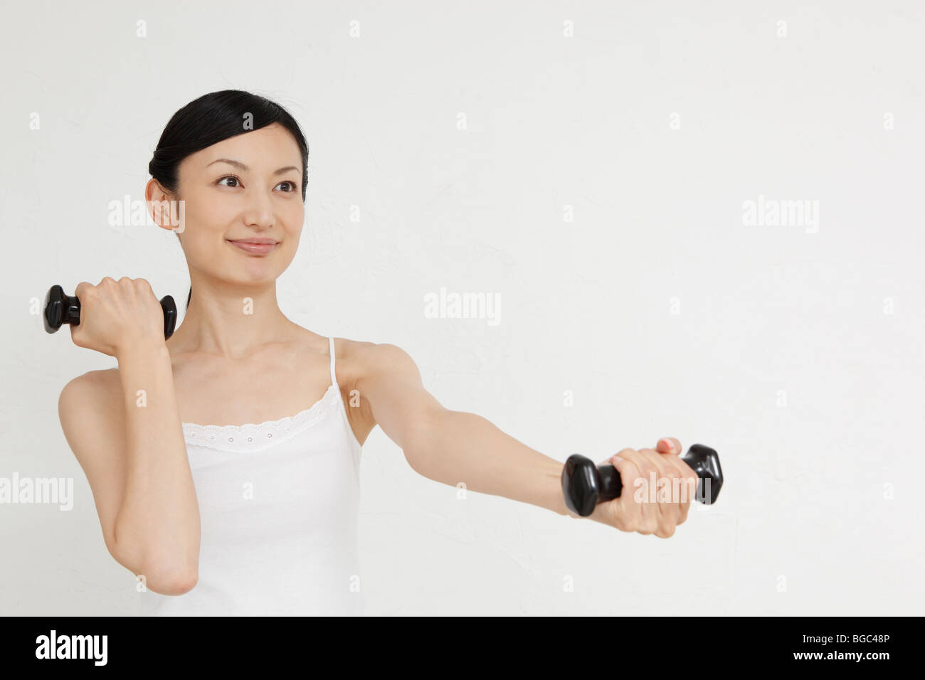 Mid adult woman holding dumbbell - Stock Image