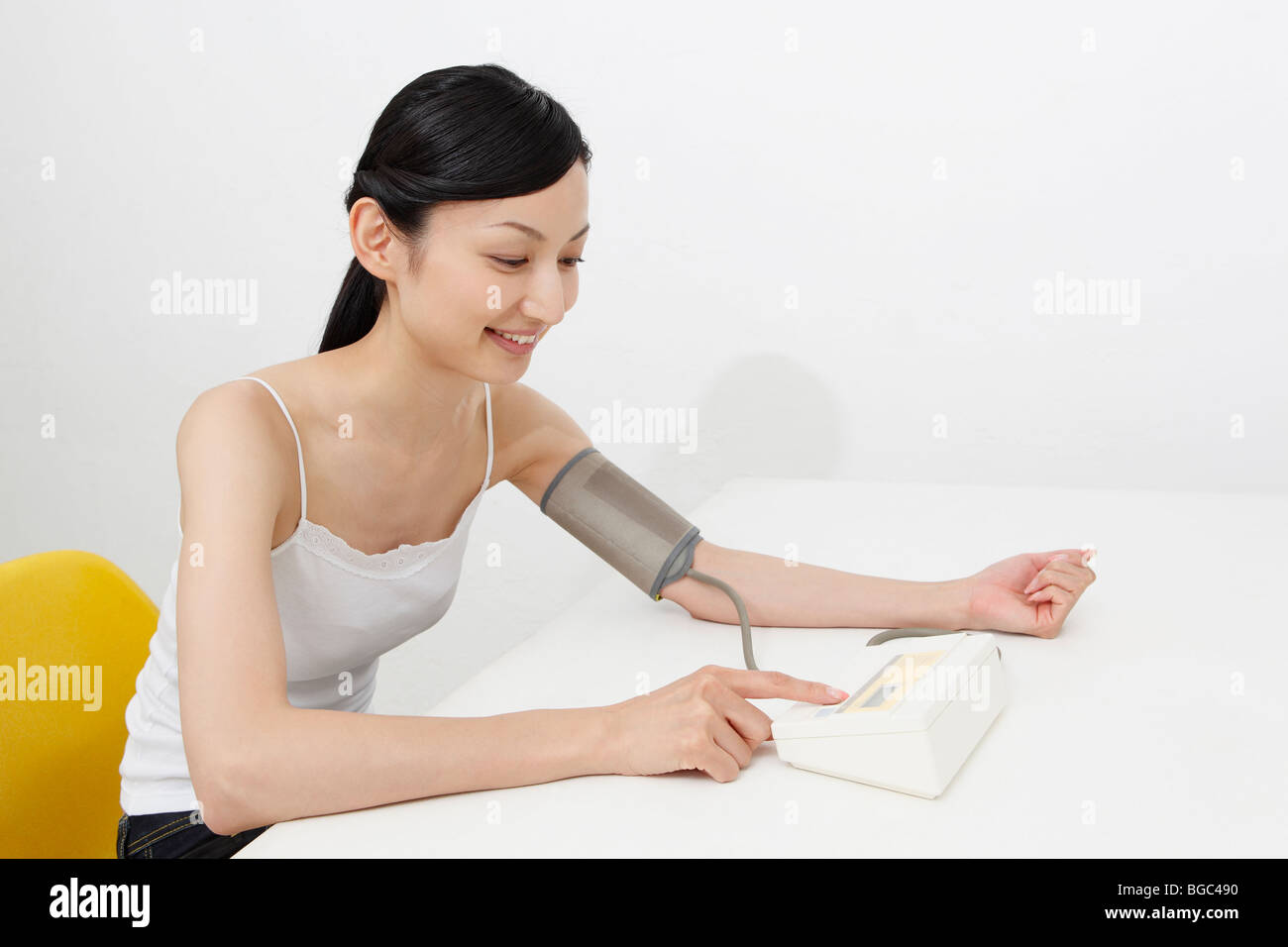 Mid adult woman checking blood pressure - Stock Image