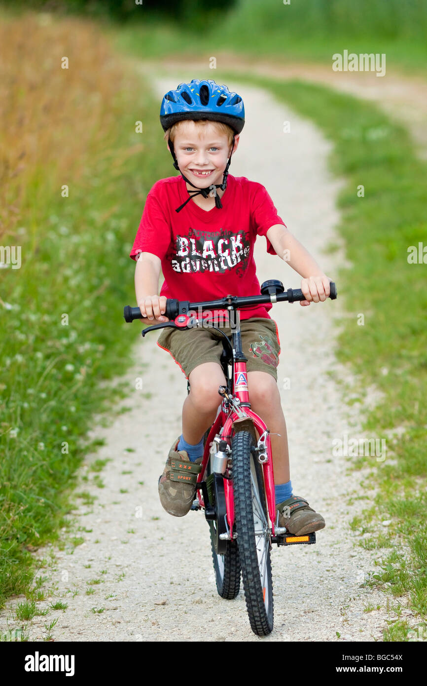 A boy, 7 years, riding a bicycle on a dirt road - Stock Image