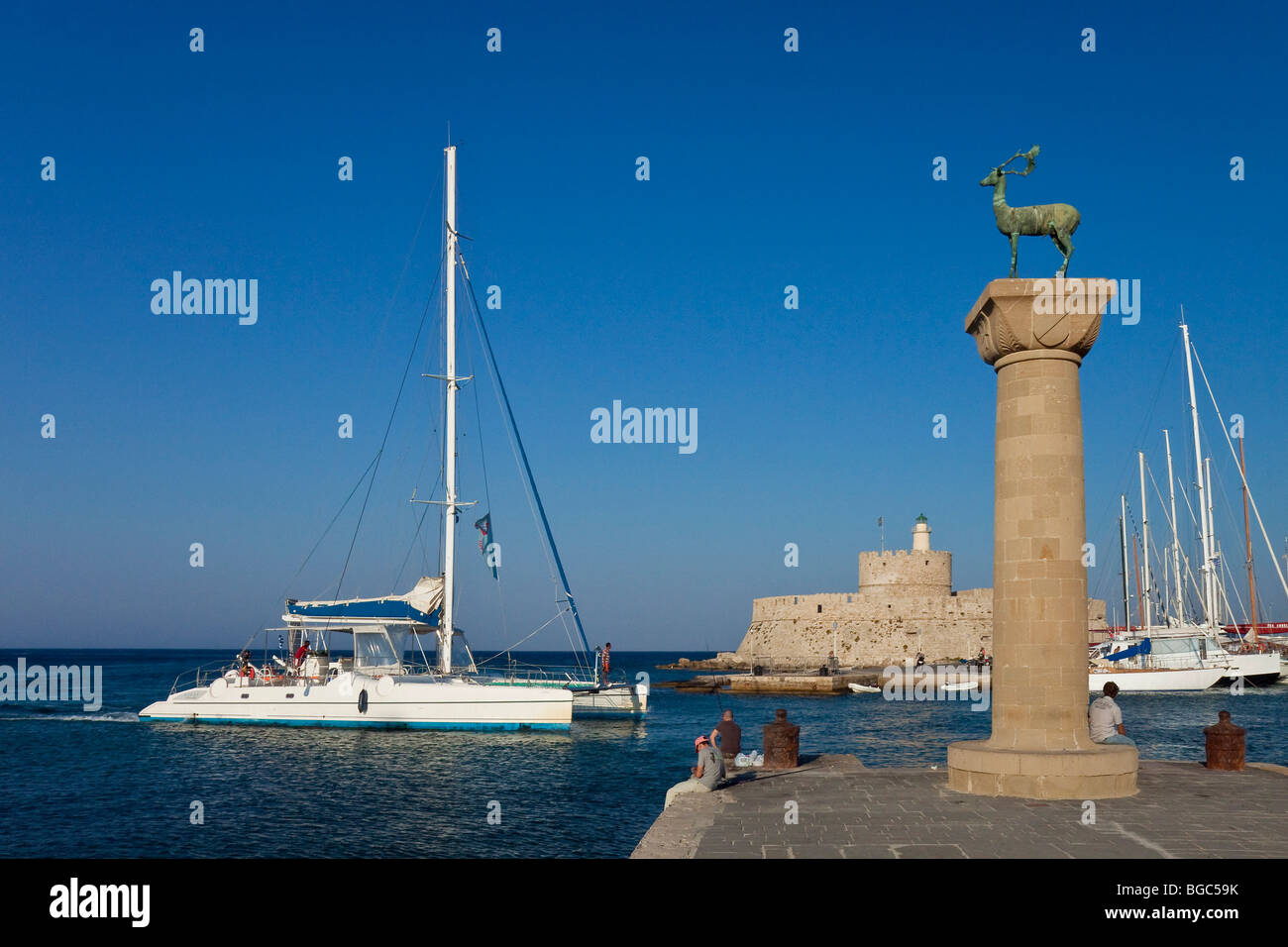 Landmark stag, a catamaran passes the harbor entrance, Rhodes town, Rhodes island, northern part of Greece, Aegean - Stock Image