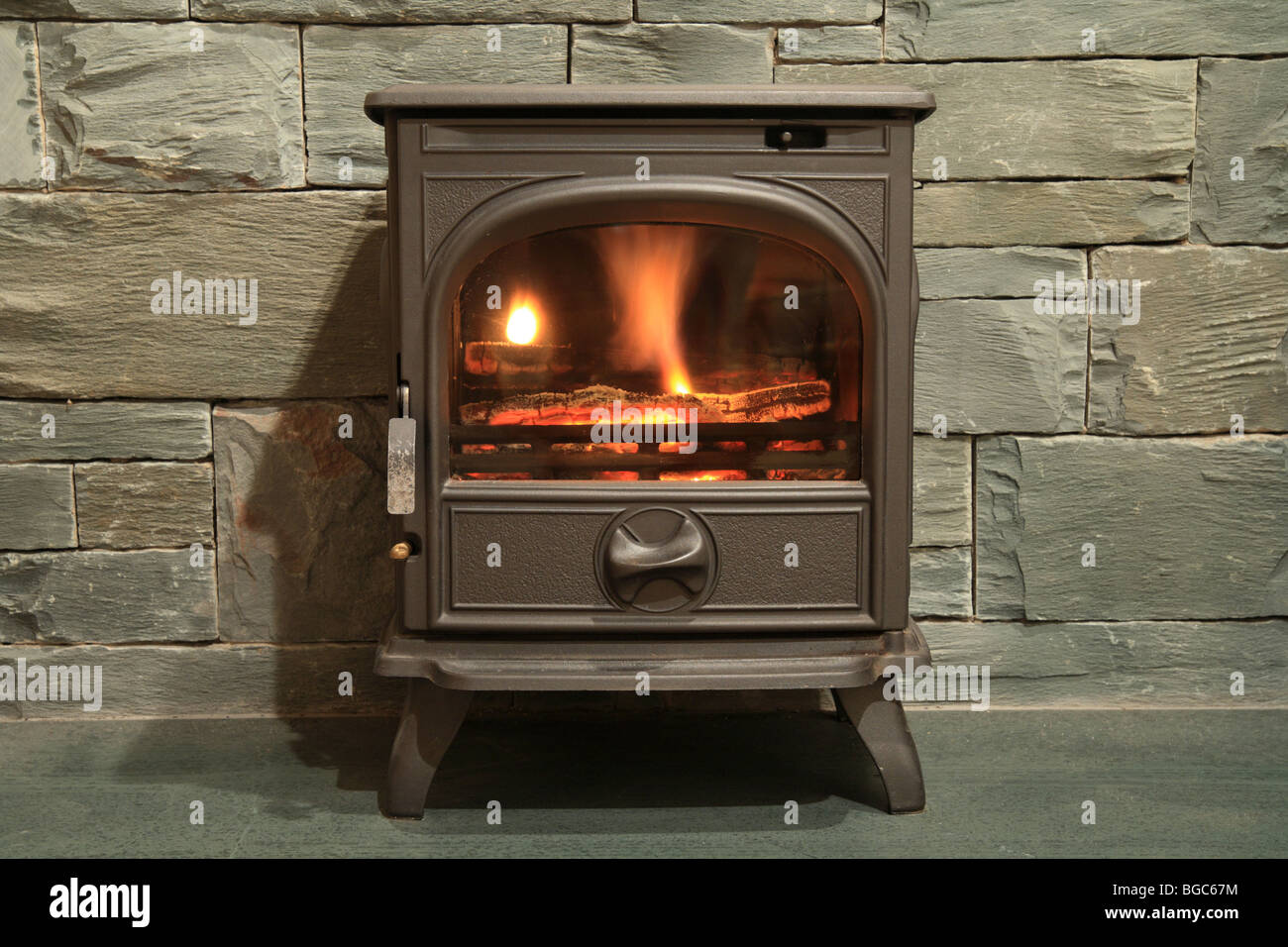 'Wood burning stove' standing on a Slate hearth with a slate surround, fireplace - Stock Image